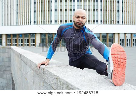 Young man in activewear practicing physical exercises outdoor