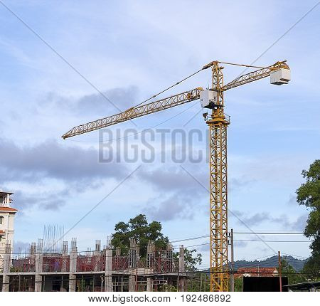 Yellow construction tower crane in working time