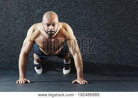 Active muscular man doing push-ups in gym
