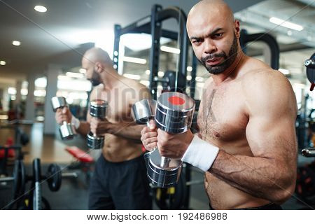 Young man looking at camera while exercising in gym
