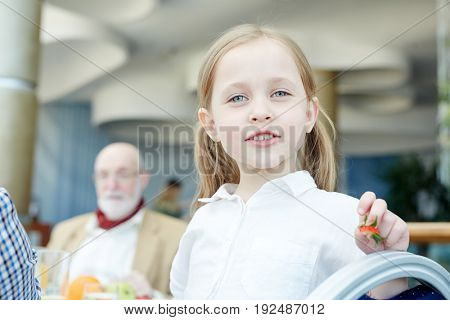 Cute little girl looking at camera while eating
