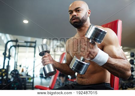 Young man sweating while exercising with dumbbells
