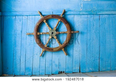 Blue wall, superannuated, old wooden steering of a vessel