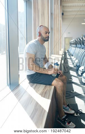Young man in sportswear sitting on window sill and having rest after workout
