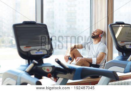 Restful sportsman enjoying music in headphones