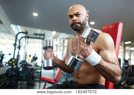 Strong athlete with dumbbells exercising in gym