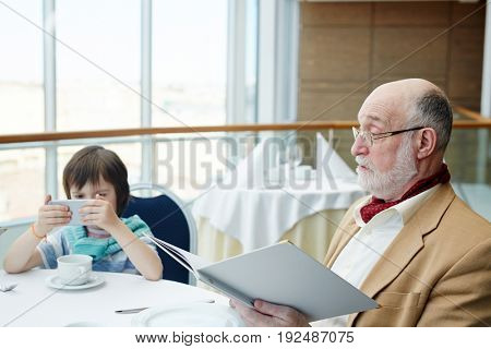 Mature man with menu and his grandson with gadget near by