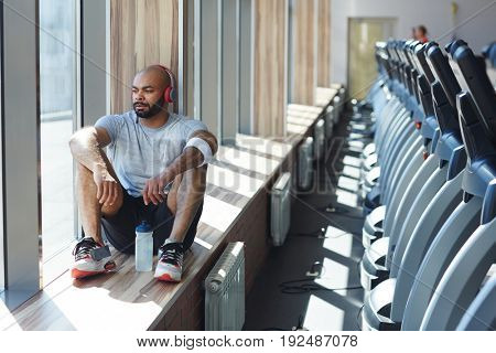 Restful sportsman looking through window during rest after workout