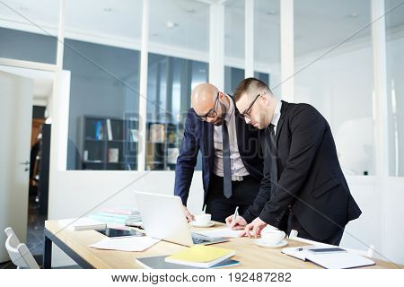 Businessman signing contract with new partner near by