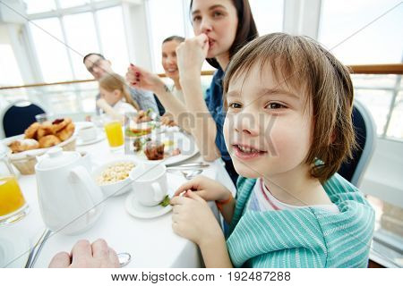Little boy talking by breakfast with his family near by