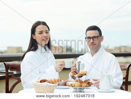 Happy couple having tea with fresh buns on balcony