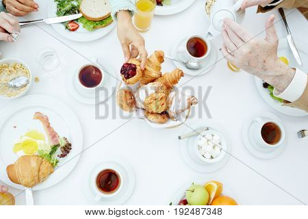 Human hand taking sweet bun during family breakfast