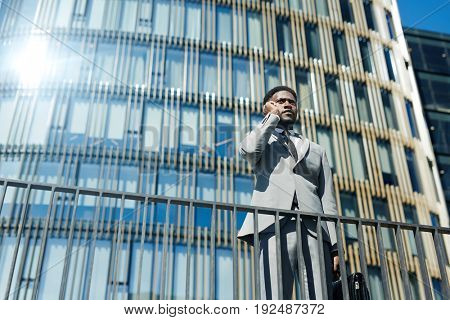 Businessman communicating on cellphone in urban environment