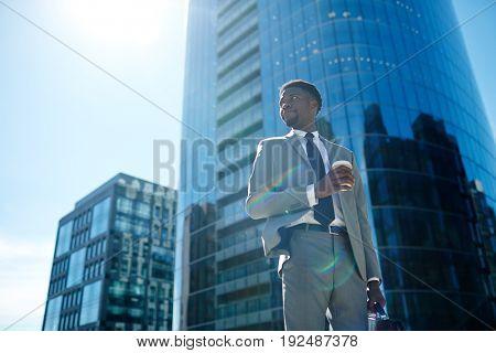 Businessman having drink in urban environment
