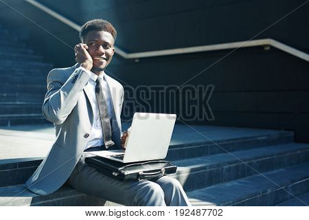 Smiling agent with laptop speaking to client on smartphone