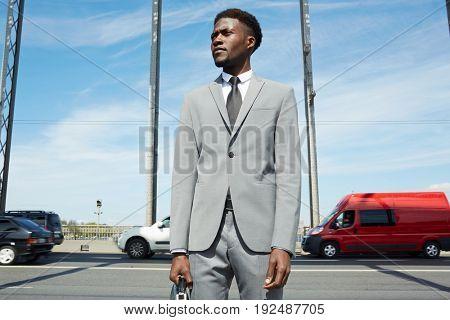 Modern entrepreneur in formalwear on background of city traffic