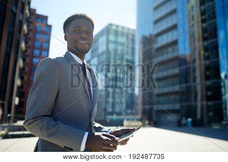 Young specialist with touchpad on b ackground of urban architecture