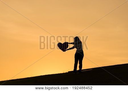 Silhouette of asian lady standing on hill and holding heart over her head with two hands during sunset time to show her love on Valentines day selective focus