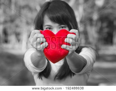 Asian lady looking forward with hands holding red soft heart small pillow tightly to show her strong feeling of sad love on Valentines day selective focus with black and white tone