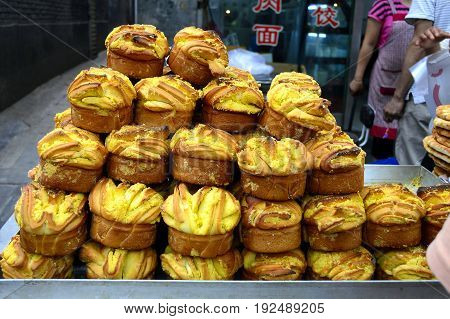 China Xian Muslim food street. Local stall sells the giant muffin-shaped bread. Muslim street is one of the key attractions in the ancient capital Xian which has many famous local snack food.