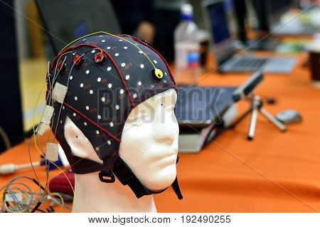 The electroencephalogram (EEG) head cap with flat metal discs (electrodes) attached to a white plastic model's head shown in a science exhibition with laptops blurred at the background. EEG is widely used in brain science research and clinical application