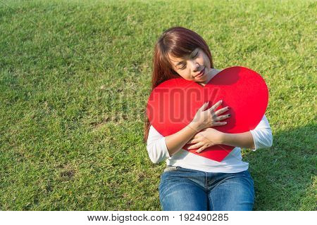 Asian single lady siting on green yard and hugging her big red heart of Valentines day concept with happy smile and copy space for text decoration design