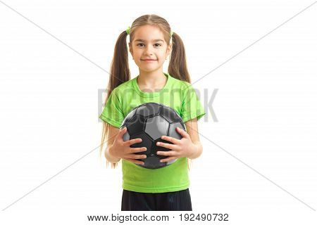 cutie little girl in green shirt holding a soccer ball in hands isolated on white background