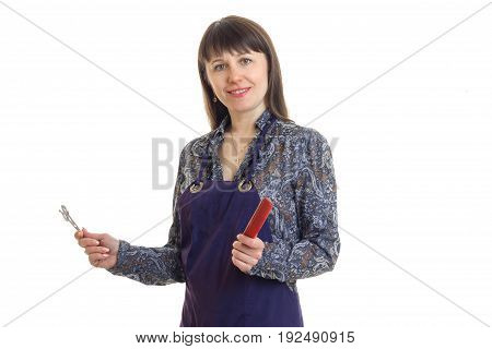 Woman stylist in an apron with tools in hands smiling on camera isolated on white background
