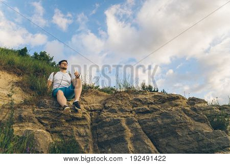 man sitting on the peak alone with his minds, clody wheather