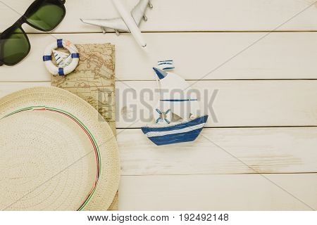 Top view accessories to travel beach.vintage sailboat with shell bicycle on wooden background.
