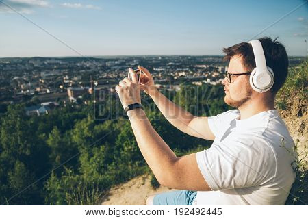 man taking picture on the top of the hill on sunset