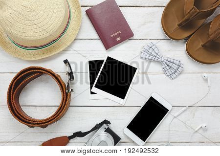 Top view accessoires to travel concept.White mobile phone hat passport camera photo sandal on wood table.