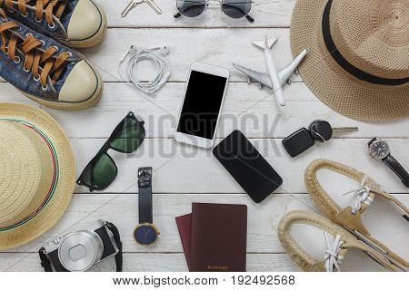 Top view women and man for essentials to travel concept.Black&White mobile phone airplane hat passport watch sun glasses shoes camera watch on wood table.
