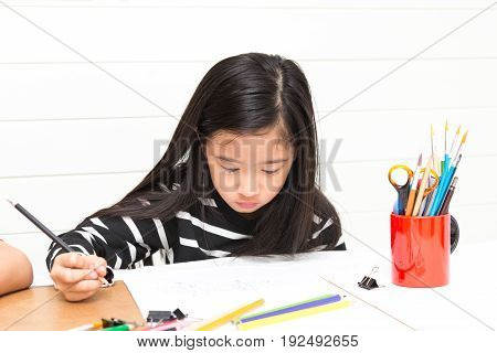 Asian girl kid concentrates on drawing cartoons by pencil over table and light wall background with friends