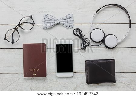 Top view accessories to travel with man clothing concept. bow tie passport on wooden background.eyeglassesheadphonewallettree on wood table.