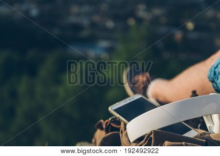 man sits on the ground chating on the phone, sunset