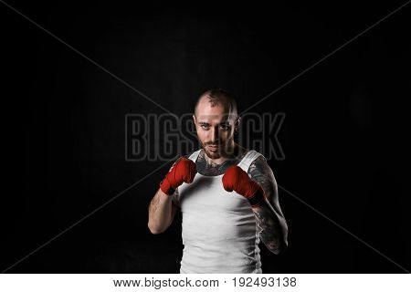 Martial arts sports kickboxing fitness and bodybuilding. Waist up portrait of handsome athletic muscular kickboxer dressed in white t-shirt holding fists in front of him showing his readiness