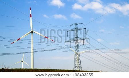 High voltage tower and wind turbines against blue sky