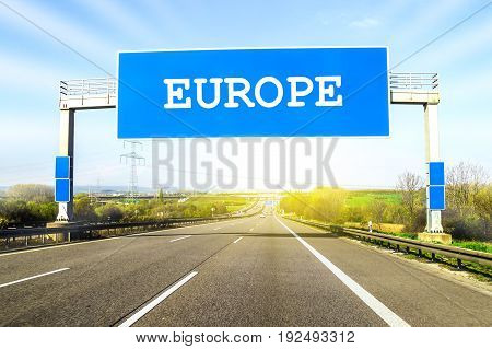 Blue freeway sign over the road on sunny day with word Europe on it