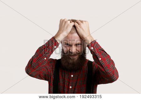 Portrait of frustrated young Caucasian businessman in checkered shirt feeling stressed looking at camera with painful expression on his face holding head while suffering from headache or migraine