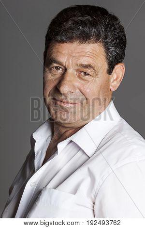 An elderly man with black hair in a white shirt smirks
