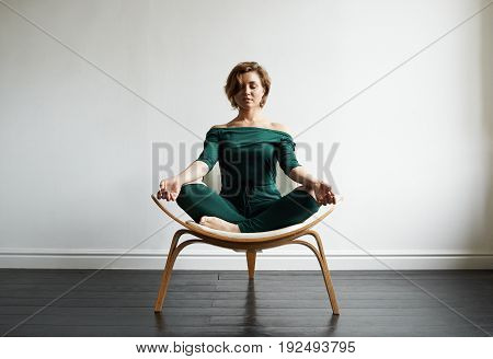 Attractive smiling young Caucasian woman in stylish jumpsuit sitting on chair in lotus pose in spacious empty room keeping eyes closed meditating practising yoga feeling peaceful and relaxed