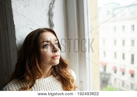 Headshot of attractive young woman with mysterious blue eyes and long curly hair standing by the window having pensive dreamy look dreaming about something or contemplating urban view outside