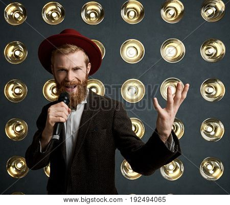 Portrait of stylish extravagant young bearded entertainer announcing next performer during concert standing on stage against light decoration background talking to audience using microphone