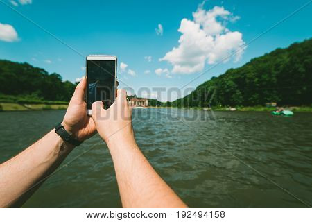 mans hands hold phone, taking picture of the lake in sunny day