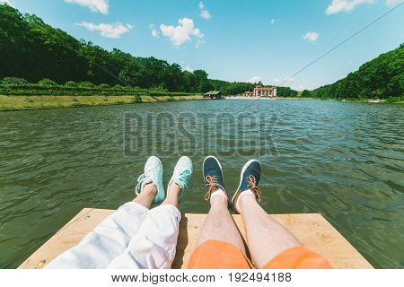 couple legs on pair looking on lake, first person view