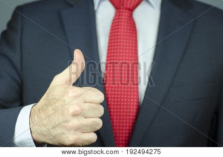 A close-up view of a manager's hand in a suit and a red tie with thumb up