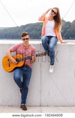 Love romance music talent passion dating concept. Girl listening to serenade. Young boy playing guitar to his lady.