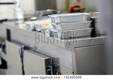 Take away food in foil boxes in Chinese restaurant kitchen Unrecognizable food ready for home delivery Home delivery concept Modern lifestyle concept Chinese food concept