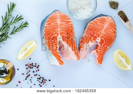steaks of salmon with a sprigs of rosemary lemon pepper sea salt on a white cutting board top view.